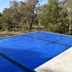 swimming pool covered with blue custom solar cover