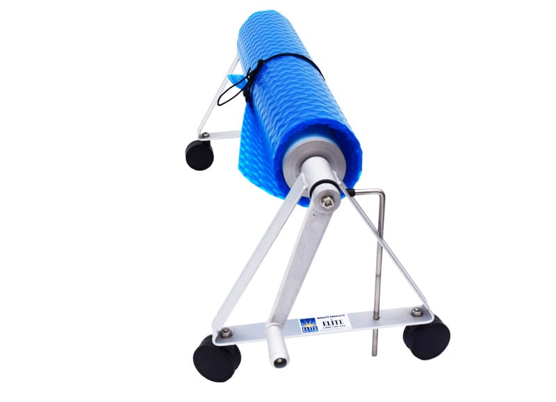 A blue swimming pool cover in a deluxe windable roller with wheels