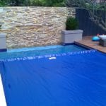 Swimming Pool with a cover on top and a brick wall in the background