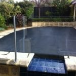 Outdoor swimming pool covered with black mesh cover