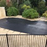 Uncommonly shaped residential Swimming Pool covered with a custom black mesh cover