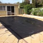 A rectangle wimming Pool covered with black mesh cover