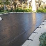 Residential Swimming Pool covered with black mesh cover next to a forest