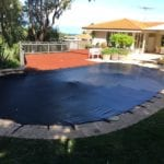 Residential Oval shape Swimming Pool covered with black mesh cover