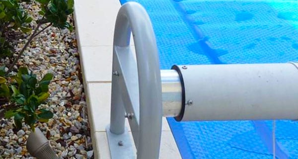 A closeup of a white semi-automatic swimming pool cover roller