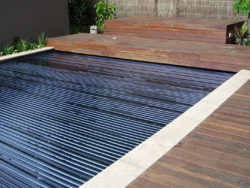 A swimming pool with a dark blue rigid cover with wooden external areas