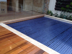 A swimming pool with a dark blue rigid cover with wooden external areas and a glass door in the back