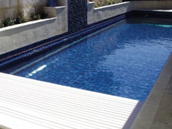 A swimming pool half-way covered with a white rigid cover