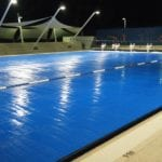 A commercial swimming pool covered with blue thermal shield in the night at a stadium