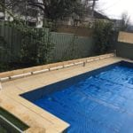 A swimming pool covered with blue pool cover