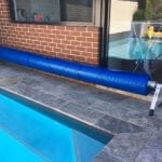 A blue swimming pool cover rolled up