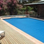 Rectangular swimming pool covered with blue pool cover