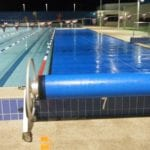 A swimming pool cover roller around the swimming pool