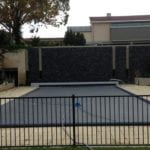 A small swimming pool covered with dark blue pool cover