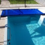 Half covered swimming pool witth blue cover