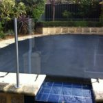 A swimming pool covered with black pool cover
