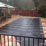 A rectangular swimming pool covered with black cover