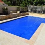 A small swimming pool covered with blue pool cover