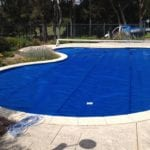 An oval shaped swimming pool covered with blue pool cover