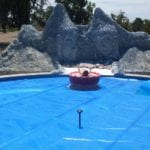 A big swimming pool and a small mountainlike structure around it