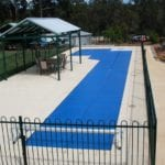 A custom shaped swimming pool covered with blue cover