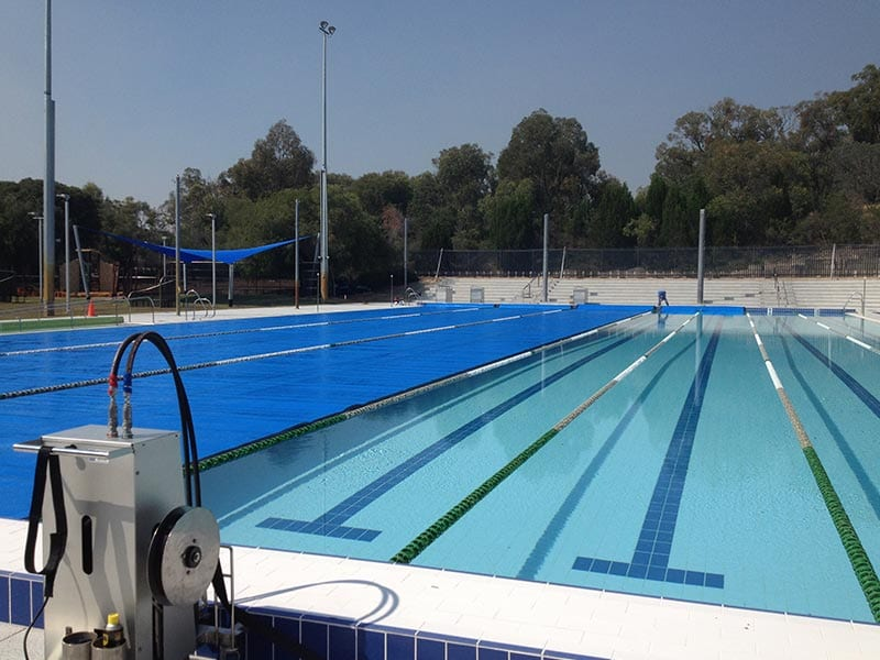 A large swimming pool half covered with blue swimming pool cover