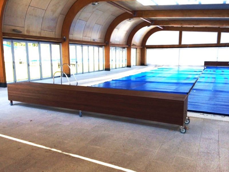 A brown wooden box bench kept around a swimming pool covered with blue cover