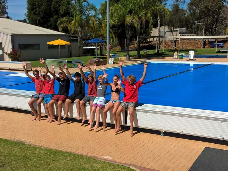 A teenagers group sitting beside swimming pool and posing for a photo by raising their hands