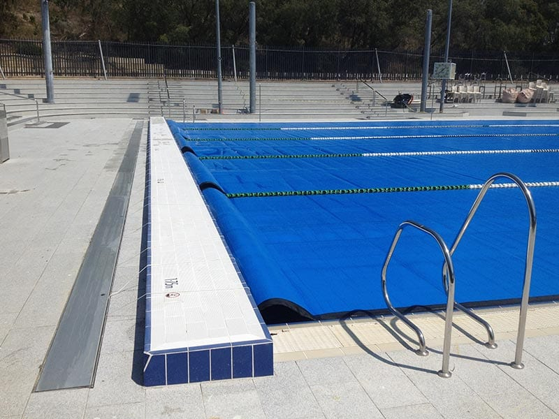 a large pool covered with blue pool cover