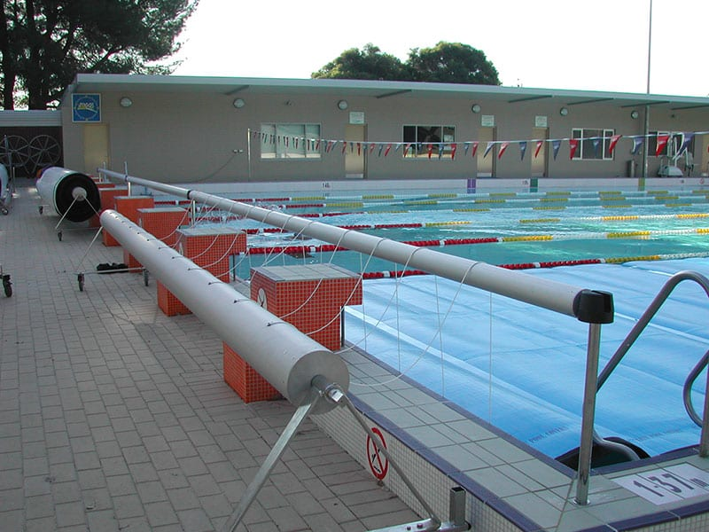 A large swimming pool and cover roller around it