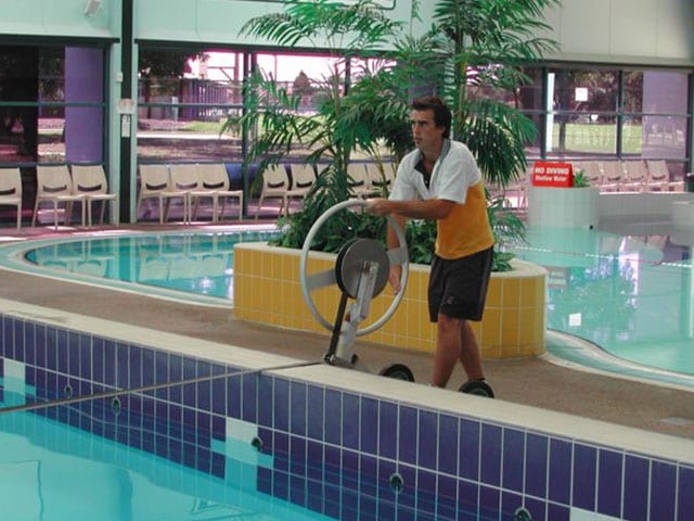 A man rolling up a swimming pool cover