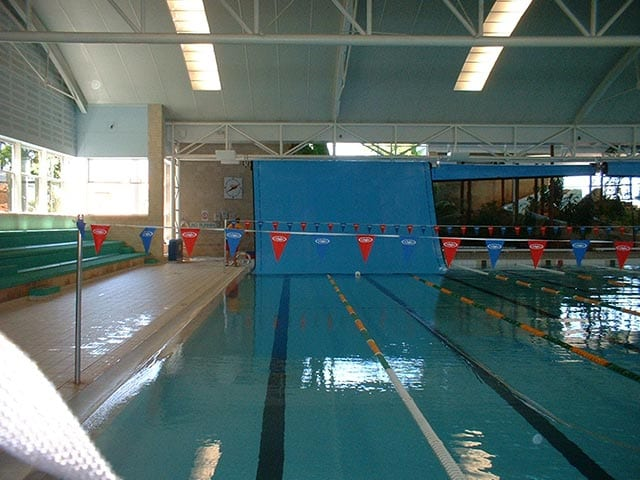 A large swimming pool with wall mounted cover around it