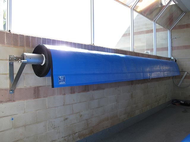 A blue pool cover rolled up on a wall mounted roller