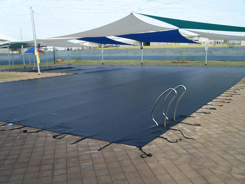 a large pool covered with black pool cover
