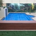 A swimming pool and a wooden bench with a colourful wall in the background