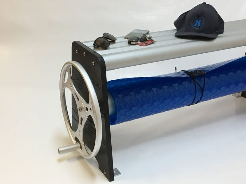Pool cover roller with sunglasses, phone, keys and a cap on top it