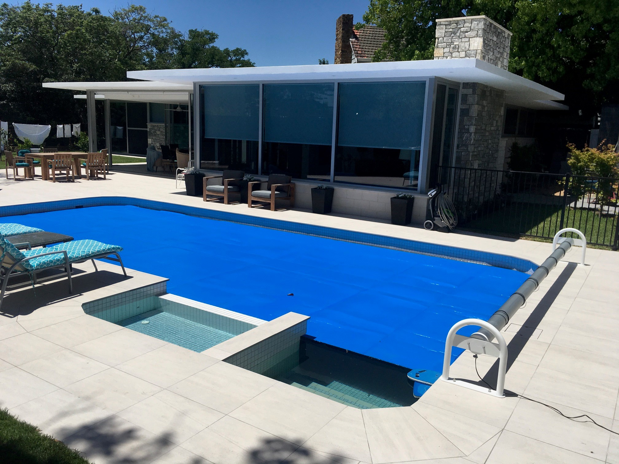 Stationary Auto Pool Cover Roller on outdoor pool in the backyard