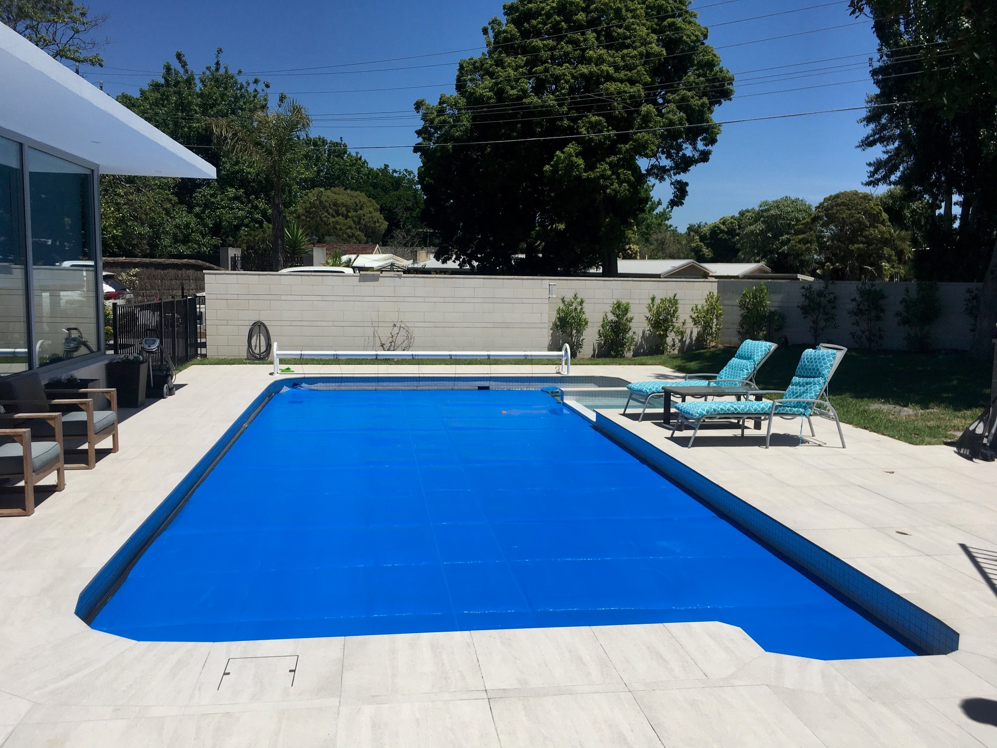 heavy Duty Auto pool cover roller in the backyard with deck chairs